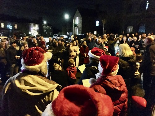 Carol singers round the tree in Crich market place