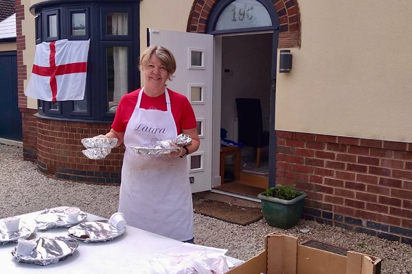 Dawn Harper with lunches and teas ready for delivery, outside her house decorated for VE Day